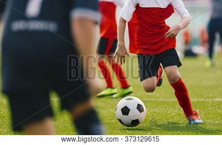 Soccer Player Dribbling, Young Footballer In Run With Ball. Boys Kicking Sports Soccer Game On Sunny