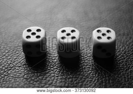 Three Dice With Fives On A Black Leather Table. Bw Photo