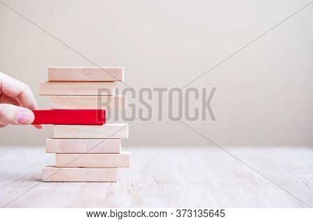 Businessman Hand Placing Or Pulling Red Wooden Block  On The Tower. Business Planning, Risk Manageme