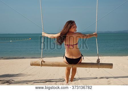 Brunette Girl Swings On Sand Beach And Looks At Camera Against Blue Sky Backside View