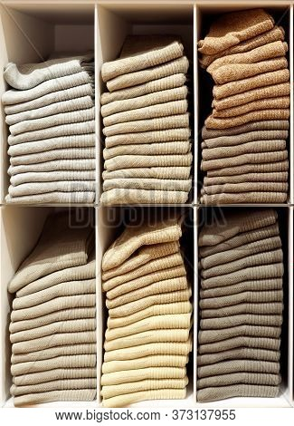 Shelves With Evenly Folded Pastel-colored Pullovers Closeup