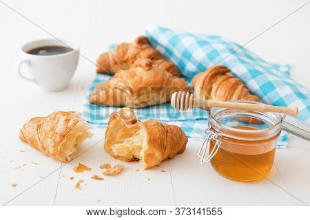 French Style Breakfast, A White Wooden Table With Cup Of Fresh Black Coffee, Croissants And Glass Bo