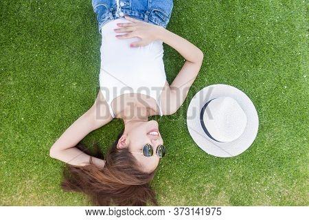 Beautiful Woman Is Laying Down On Green