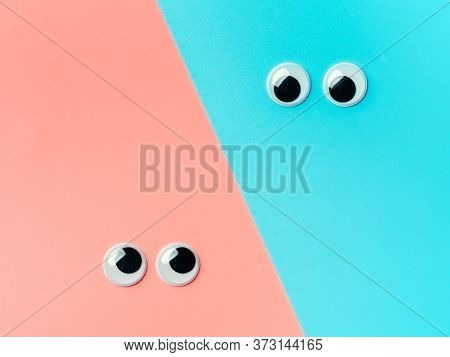 Googly Eyes On Blue An Pink Background. Top View Or Flat Lay. Plastic Toy Eyes On Turquoise Backgrou