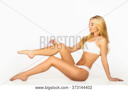 Woman Removing Hair On Legs With Razor. Woman Shaving Legs In Bathroom. Spa, Depilation And Bodycare