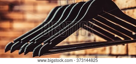 Many Wooden Black Hangers On A Rod. Store Concept, Sale, Design, Empty Hangers. Wooden Coat Hanger C
