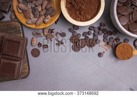 Chocolate Pieces And Drops, Cocoa Beans And Powder On Grey Background
