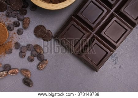 Chocolate Bar And Drops On The Grey Table