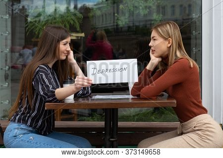Woman Holding White Sheet Paper Labeled Word Depression In Hand. Two Women Talking In Street Cafe. H