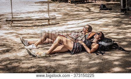 Two Girls Friends Backpackers Enjoying And Lying On Their Ranches On The Tropical Beach Sand In The