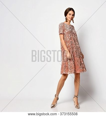 Full Length Shot Of Glamour Young Lady With Stylish Hairdo And Thick Earrings Demonstrating Sparkly