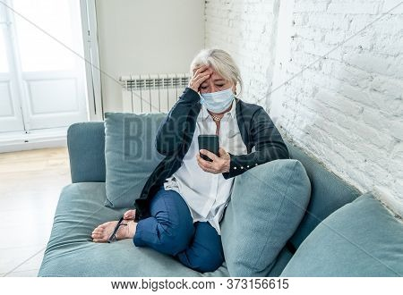 Lonely Depressed Senior Widow Woman With Protective Mask Crying On Couch Isolated At Home, Sad And W