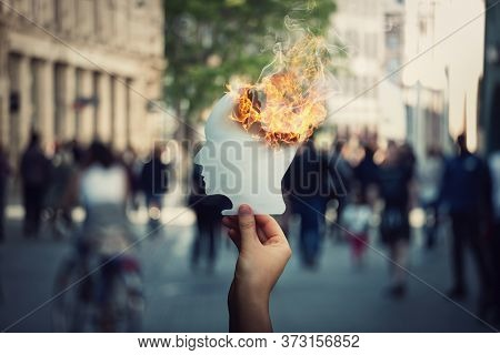Burnout And Stress Concept As Person Hand Holds A Burning, Human Head Shaped, Paper Sheet On A Crowd