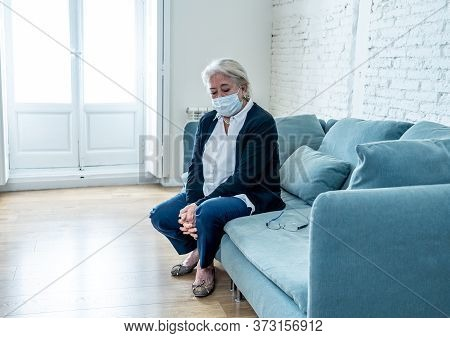 Depressed Senior Widow Woman With Protective Mask Alone At Home Feeling Sad And Missing Family