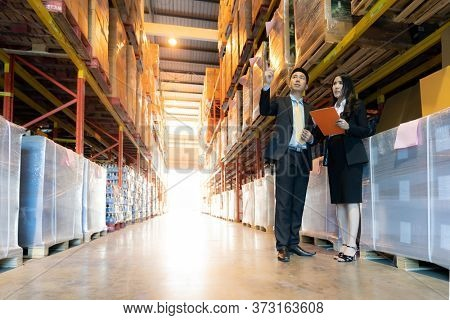 Portrait of businessman discuss with businesswoman about inventory with factory warehouse. Business distribution warehouse concept.
