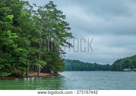 A Quiet And Peaceful Rainy Overcast Sky At The Lake With Docks And Boats In The Background On A Summ