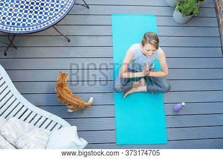 Overhead View Of Mature Woman With Pet Cat At Home Meditating With Yoga On Deck