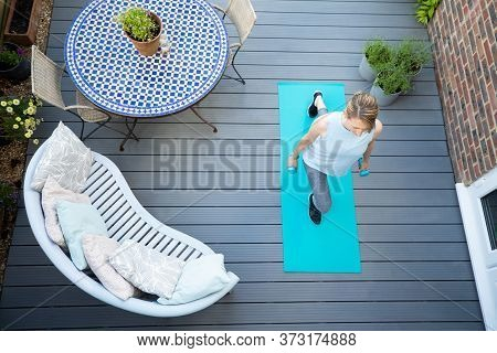 Overhead View Of Healthy Mature Woman At Home Exercising On Deck  With Dumbbell Hand Weights