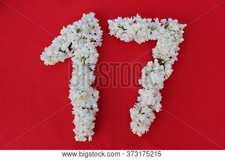 The Number 17 Is Written In White Lilac Flowers On A Red Background. The Number Seventeen Is Written