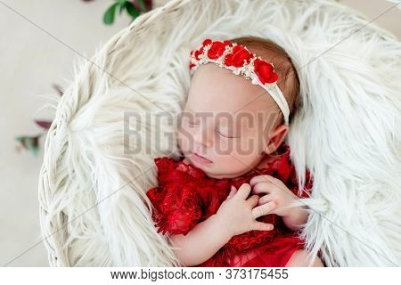 Sleeping newborn baby girl in a red dress
