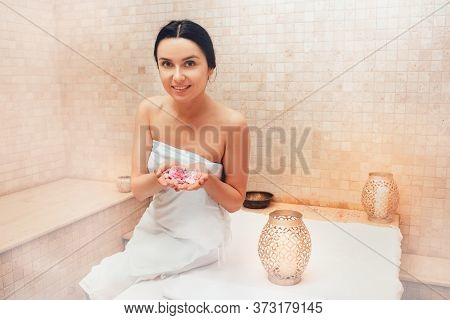 Cheerful Woman With Rose Petals In Hands, Sitting In A Turkish Hammam. Traditional Turkish Bath