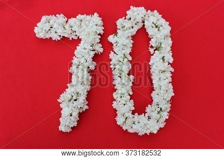 The Number 70 Is Written In White Lilac Flowers On A Red Background. The Number Seventy Is Written I