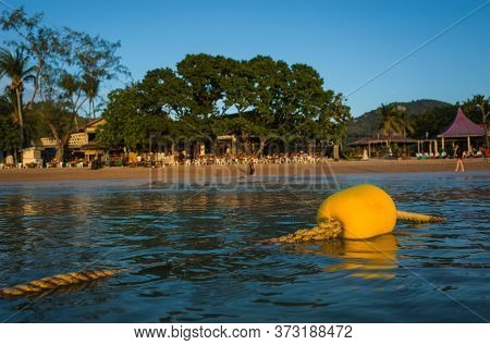Yellow plastic float buoy on thick rope in calm water overlooking the tropical island Koh Tao, Sairee beach, Thailand. Evening
