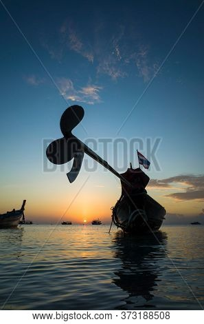 Beautiful sunset on tropical island Koh Tao, Thailand. Long tail boat engine propeller silhouette