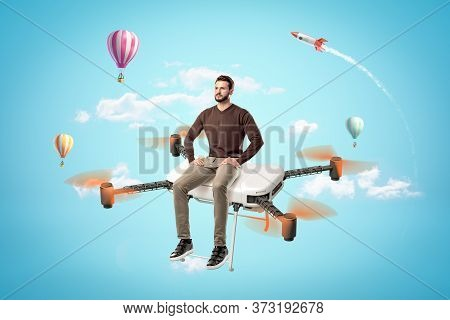 Serious Handsome Young Man In Casual Clothes Sitting On Big Quadcopter In Blue Sky With Hot Air Ball