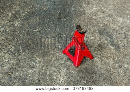 Red Axle Stand On Floor. Red High Lift Jack Stand On The Floor. Red Extendable Jack Stands Are Used
