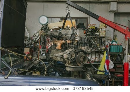 Engine Hanging On Crane Hook On Car Repair Service. Photo Of Old Engine Hanging On A Cable. Engine H