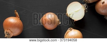 Unpeeled Raw Yellow Onions On A Black Background. Flat Lay, Overhead, From Above.