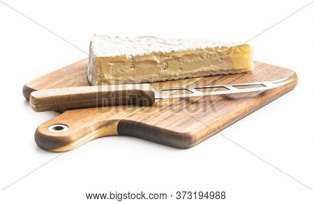 Brie cheese. White soft cheese with white mold on wooden cutting board isolated on white background.