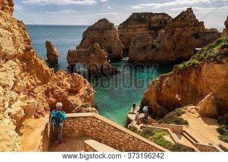 Lagos, Portugal - 6 March 2020: Tourist Looking At The Cliffs At Ponta Da Piedade