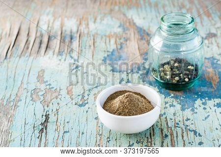 Black Ground Pepper In A White Bowl And A Can Of Peppercorn On An Old Wooden Table. Spice To Improve