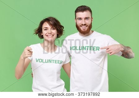 Smiling Two Young Friends Couple In White Volunteer T-shirt Isolated On Green Background. Voluntary