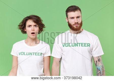 Perplexed Shocked Two Young Friends Couple In White Volunteer T-shirt Isolated On Pastel Green Backg