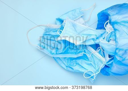Disposable Mask Thrown In The Trash. Discarded Surgical Masks. Medical Waste With Copy Space On A Bl