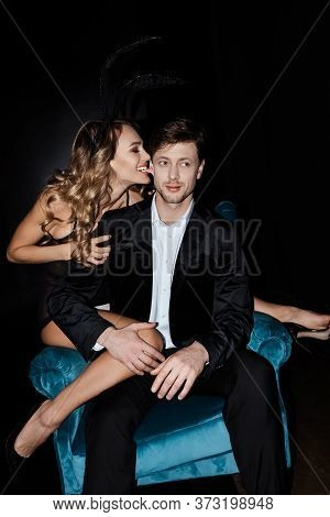 Woman Biting Ear Of Handsome Boyfriend In Suit Sitting In Armchair Isolated On Black