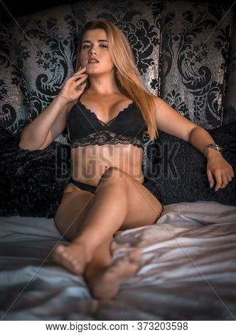 Boudoir Session With A Young Blonde Caucasian Woman On Top Of A Bed With Black Lingerie, In A Circul
