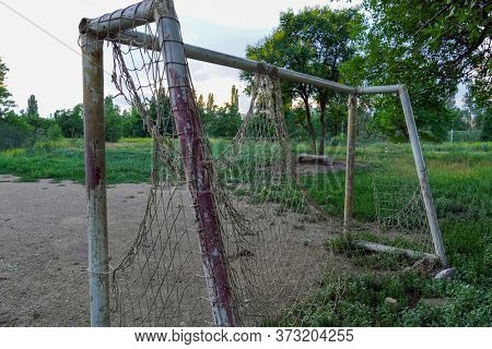 abandoned football field, goal with a torn net in a vacant lot