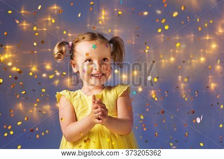 A Girl In A Yellow Dress Claps Her Hands Looks Away And Smiles, Freckles Of Stars On Her Face, Flyin