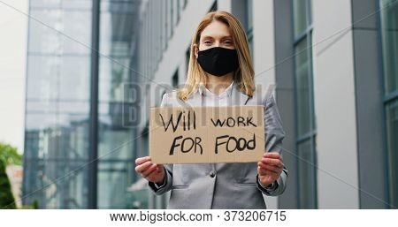 Portrait Of Caucasian Young Woman In Mask Demonstrating Poster With Words Will Work For Food. Female