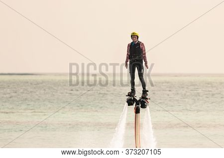 Rangali, Maldives - February 14th, 2019: A Woman Suspended In The Air Using A Water Jet Pack In Mald