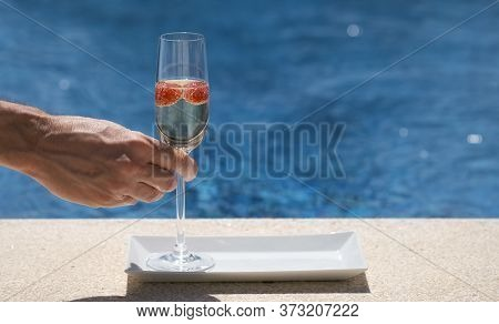 Man Takes A Glass With Champagne Or Prosecco With Raspberry On Swimming Pool Or Sea Blurred Backgrou