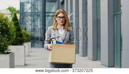 Sad Young Caucasian Beautiful Woman In Glasses Walking The Street, Carrying Box With Stuff After Fir