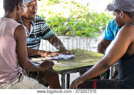La Dique, Seychelles - February 4th, 2019: Four Local Men Playinig Domino Outdoors In La Digue, Seyc