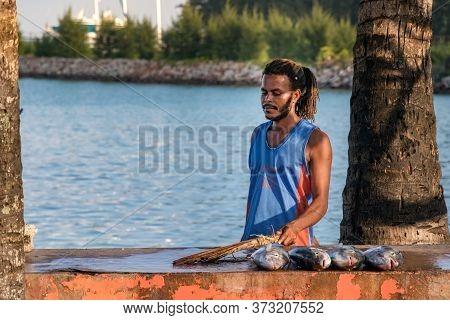 Praslin, Seychelles - February 5th, 2019: Portrait Of A Local Fisherman Selling Fresh Fish On A Tabl