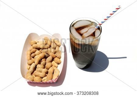 Peanuts and a Cola with Ice. Isolated on white. Room for text. Roasted Peanuts and a Glass of Cola with Ice and a Red, White and Blue Paper Straw.