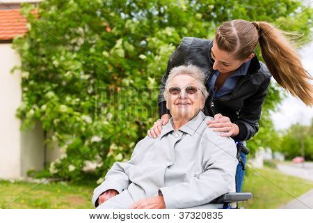 Young woman is visiting her grandmother in nursing home having a walk with here in a wheelchair